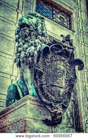Vintage retro hipster style travel image of Bavarian lion statue at Munich Alte Residenz palace in Odeonplatz with overlaid grunge texture. Munich, Bavaria, Germany