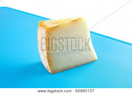 piece of light gouda cheese on blue board