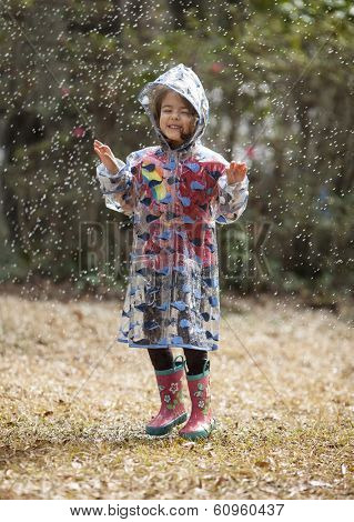 little girl in raincoat and boots playing in the rain