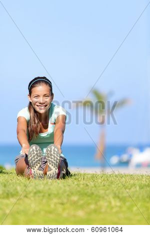 Fit fitness woman doing stretching exercises outdoors. Girl doing hamstring leg stretching exercise and stretches. Female sports model exercising outdoor in summer. Beautiful multiracial Asian girl.