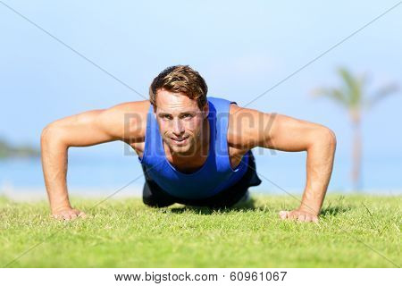 Push-ups - fitness man training push up outside in grass in summer. Fit male athlete working out cross training exercising outdoor. Caucasian muscular sports model in his 20s.
