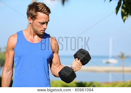 Bicep curl - weight training fitness man outside working out arms lifting dumbbells doing biceps curls. Male sports model exercising outdoors as part of healthy lifestyle.