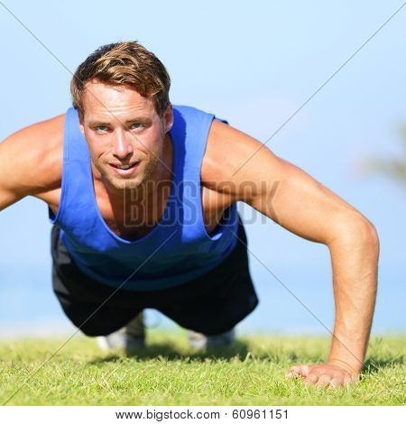 Push ups - fitness man exercising push up outside in grass in summer. Fit male athlete working out cross training outdoor. Caucasian muscular sports model in his 20s.