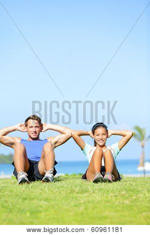 People exercising - Couple doing sit ups outdoors. Fitness couple doing situps exercise during outside cross training workout. Happy young multiracial couple, Asian woman, Caucasian man.
