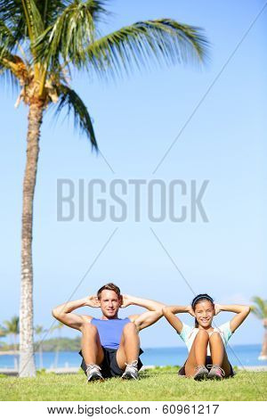 People training sit ups outside. Fitness couple doing situps exercise during outdoor cross training workout. Happy young multiracial couple, Asian woman, Caucasian man.
