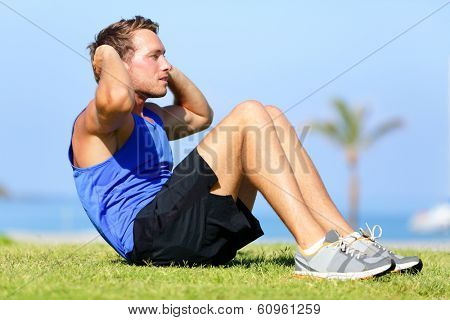Sit-ups - fitness man training sit up outside in grass in summer. Fit male athlete working out cross training exercising. Caucasian muscular sports model in his 20s.