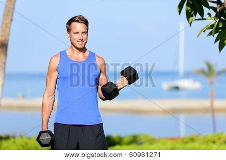 Fitness bicep curl - weight training man outdoors working out arms lifting dumbbells doing biceps curls. Male sports model exercising outside as part of healthy lifestyle.