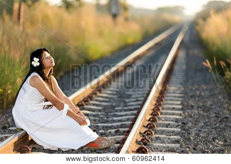 Beautiful young Thai woman meditating sitting in the last rays of the sun on a receding train track in a fresh white dress with a serene expression and her face lifted to the light