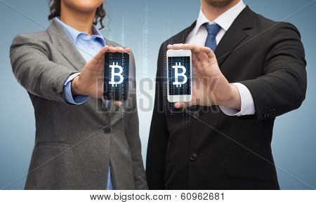 business, technology and internetconcept - businessman and businesswoman with bitcoin sign on smartphone screens