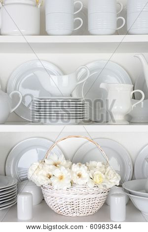 Vertical closeup of a  basket of roses on the shelf of a cupboard full of white plates. Items include, plates, saucers, bowls and a gravy boat.