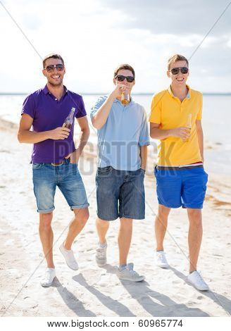 summer, holidays, vacation and people concept - group of male friends having fun on the beach with bottles of beer or non-alcoholic drinks