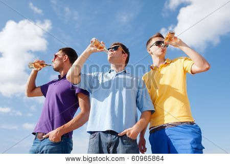 summer, holidays, vacation, happy people concept - group of male friends having fun on beach with bottles of beer or non-alcoholic drinks