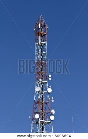 Communication tower with parabolic antennas enclosed in domes