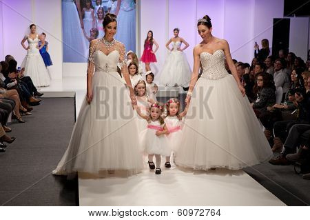 ZAGREB, CROATIA - FEBRUARY 15, 2014: Fashion models in wedding dresses with children models dressed as little bridesmaid on 'Wedding fair'