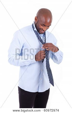 Portrait Of A Young African American Business Man Knotting A Tie - People