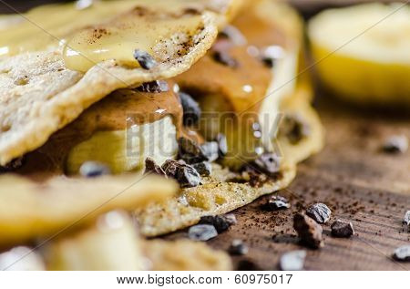 Closeup of banana and choco chips pancake with syrup on it