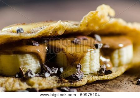 Closeup of pancake made with bananas; choco chips and syrup on table