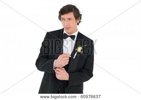 Groom in tuxedo adjusting cuff link on white background