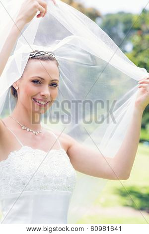 Portrait of happy beautiful bride unveiling self in garden