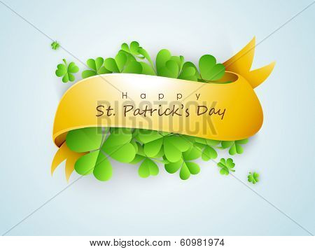Happy St. Patrick's Day celebrations concept with beautiful green Irish lucky shamrock leaves with golden ribbon on blue background.