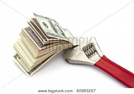 Wrench and bills of U.S. dollar currency isolated on white background