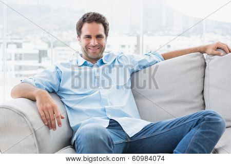 Happy handsome man relaxing on the couch looking at camera at home in the living room
