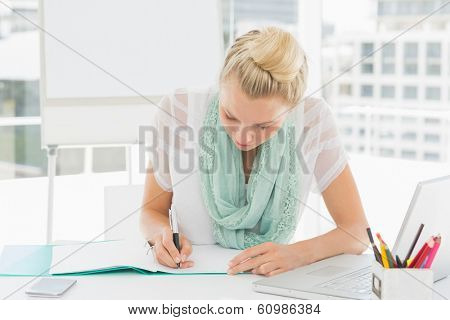 Casual young woman writing notes in a bright office