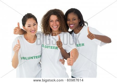 Attractive team of volunteers giving thumbs up at camera on white background