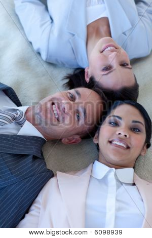 Business Team On Floor With Heads Together Smiling