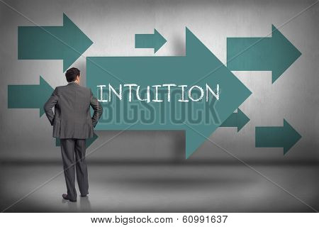 The word intuition and businessman with hands on hips against blue arrows pointing
