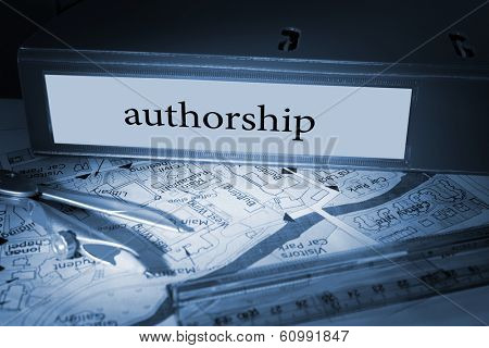 The word authorship on blue business binder on a desk
