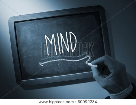 Hand writing the word mind on black chalkboard