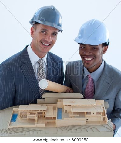 Smiling Engineers With Hard Hats Holding A Model House