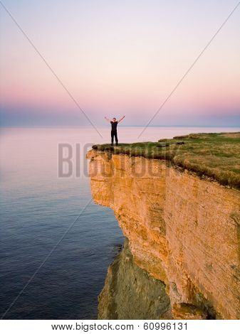 young man standing on the cliff with spreaded hands