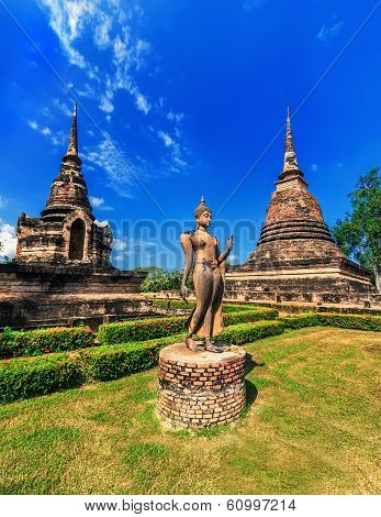 Ancient Architecture Of Buddhist Temples In Sukhothai Historical Park. Statue Of Walking Buddha At S