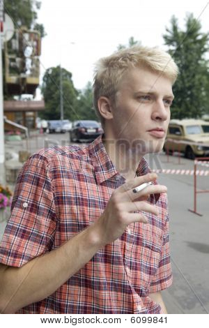 young blond man smoking in street