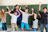 Successful Teacher and students jump in front of a blackboard with math work in a classroom or class
