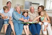 stock photo of storybook  - Happy multigeneration family reading storybook in living room at home - JPG