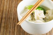 picture of wanton  - Extreme close up horizontal photo of freshly made wonton with chopsticks on top of white bowl