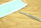 stock photo of scalpel  - Scalpel stainless steel placed on the brown table and a mask is placed nearby - JPG