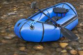 a blue packraft (one-person light raft used for expedition or adventure racing) with a kayak paddle