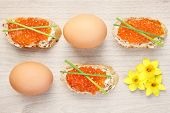 A picture of an Easter composition of eggs caviar and flowers over natural background