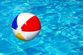 stock photo of pool ball  - Beach ball floating in swimming pool abstract concept for summer vacations - JPG