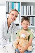 Portrait of friendly female doctor with boy holding teddy bear in clinic