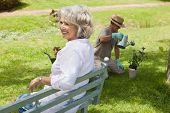image of sitting a bench  - Happy woman sitting on bench while man watering young plant at the park - JPG