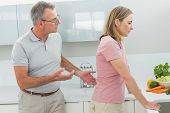 stock photo of argument  - Unhappy couple having an argument in the kitchen at home - JPG