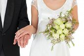 Mid section of bride and groom with rose bouquet over white background