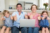 pic of three sisters  - Portrait of happy family with laptop showing thumbs up sign while sitting on sofa at home - JPG