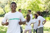 picture of environmentally friendly  - Portrait of smiling volunteer showing thumbs up with friends disucssing in background - JPG
