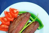 meat savory : grilled beef fillet mignon served on blue plate over blue wooden table with chili pepp
